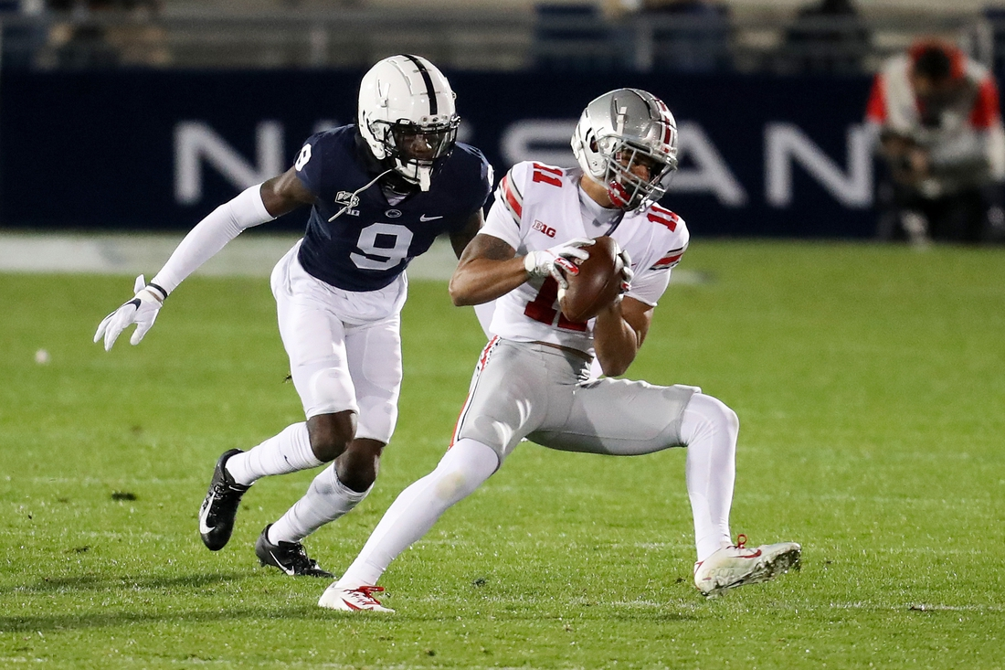 Oct 31, 2020; University Park, Pennsylvania, USA; Ohio State Buckeyes wide receiver Jaxon Smith-Njigba (11) makes a catch as Penn State Nittany Lions cornerback Joey Porter Jr. (9) attempts a tackle during the first quarter at Beaver Stadium. Mandatory Credit: Matthew OHaren-USA TODAY Sports