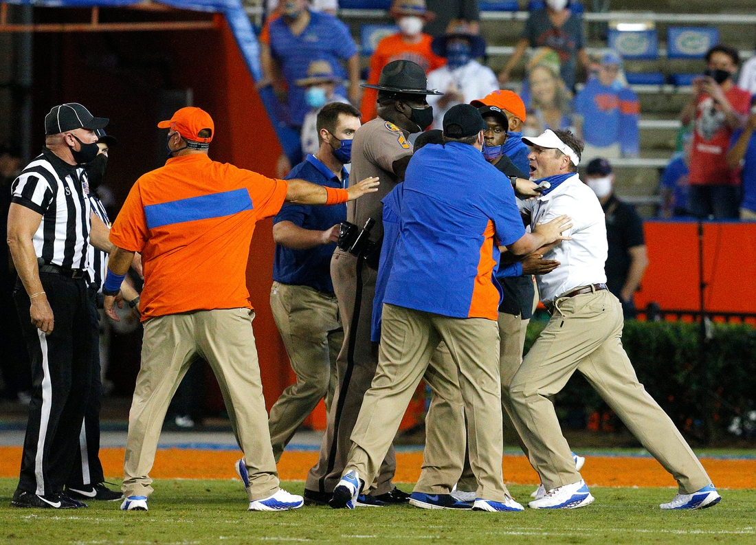 Oct 31, 2020; Gainesville, FL, USA;  Florida head coach Dan Mullen, far right, is held back by coaches and law enforcement after a fight broke out at the end of the first half during a game against the Missouri Tigers at Ben Hill Griffin Stadium.  Mandatory Credit: Brad McClenny-USA TODAY NETWORK