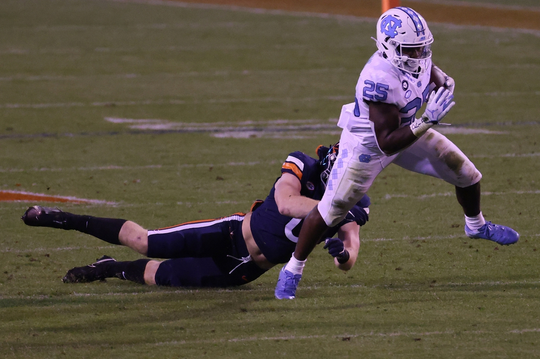 Oct 31, 2020; Charlottesville, Virginia, USA; North Carolina Tar Heels running back Javonte Williams (25) breaks a tackle attempt by Virginia Cavaliers linebacker Zane Zandier (0) while carrying the ball in the first quarter at Scott Stadium. Mandatory Credit: Geoff Burke-USA TODAY Sports