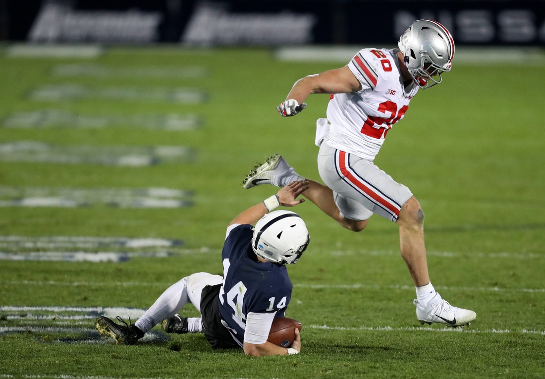 Oct 31, 2020; University Park, Pennsylvania, USA; Ohio State Buckeyes linebacker Pete Werner (20) jumps over Penn State Nittany Lions quarterback Sean Clifford (14) as he slides during the fourth quarter at Beaver Stadium. Mandatory Credit: Matthew OHaren-USA TODAY Sports