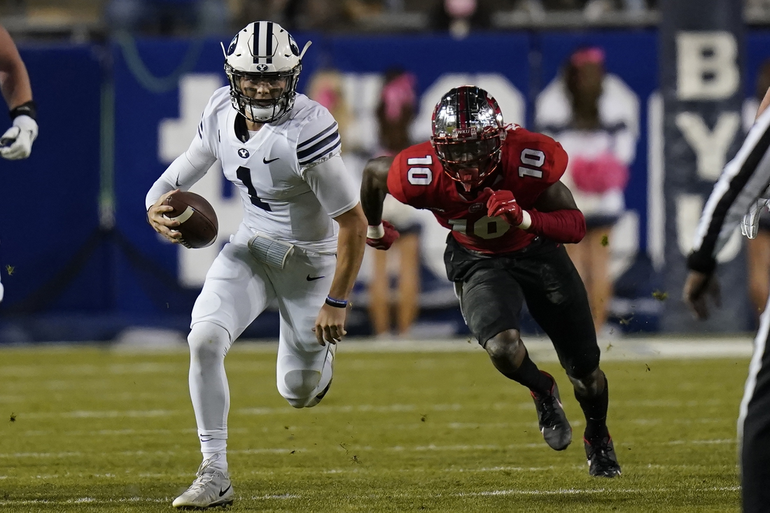 Oct 31, 2020; Provo, UT, USA; BYU quarterback Zach Wilson (1) out runs Western Kentucky defensive end DeAngelo Malone (10) in the first half of an NCAA college football game Saturday, Oct. 31, 2020, in Provo, Utah. Mandatory Credit: Rick Bowmer/Pool Photo-USA TODAY Sports