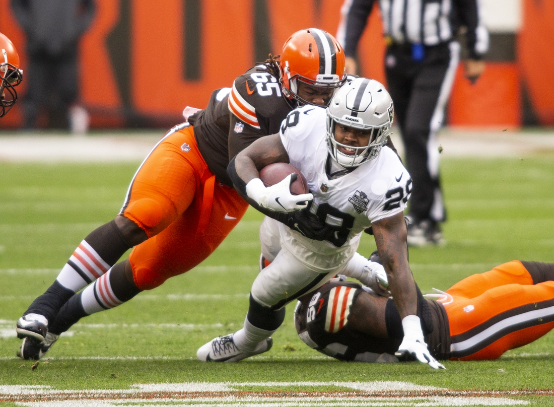 Nov 1, 2020; Cleveland, Ohio, USA; Cleveland Browns defensive tackle Larry Ogunjobi (65) tackles Las Vegas Raiders running back Josh Jacobs (28) during the first quarter at FirstEnergy Stadium. Mandatory Credit: Scott Galvin-USA TODAY Sports