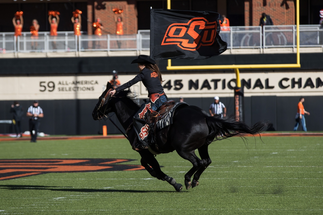Oct 31, 2020; Stillwater, Oklahoma, USA;  Oklahoma State Cowboys mascot Spirit Rider holds an OSU flag as she rides Bullet on the field after a Cowboys touchdown during the first quarter of the game against the Texas Longhorns at Boone Pickens Stadium. Texas won 41-34. Mandatory Credit: Brett Rojo-USA TODAY Sports