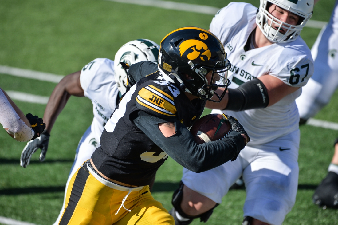 Nov 7, 2020; Iowa City, Iowa, USA; Iowa Hawkeyes defensive back Riley Moss (33) returns an interception off Michigan State Spartans quarterback Rocky Lombardi (not pictured) for a touchdown as offensive lineman J.D. Duplain (67) looks to make the tackle during the second quarter at Kinnick Stadium. Mandatory Credit: Jeffrey Becker-USA TODAY Sports