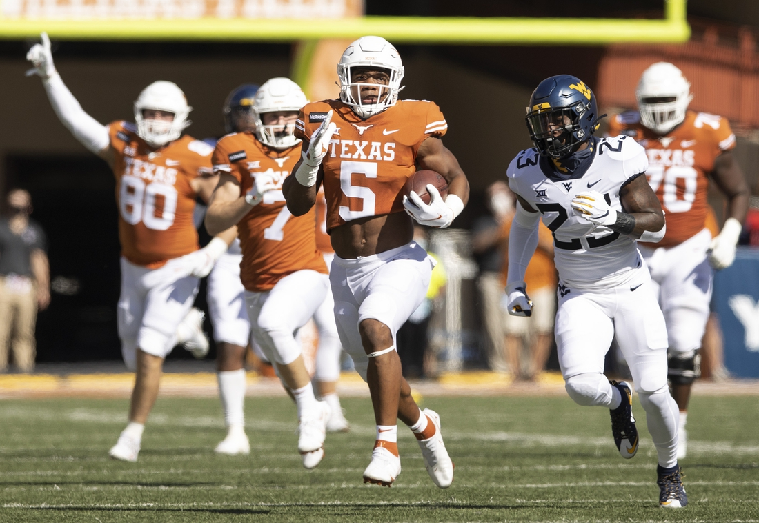 Nov 7, 2020; Austin, Texas, USA;  Texas running back Bijan Robinson makes a long run against West Virginia safety Tykee Smith in the first quarter at Royal-Memorial Stadium on Saturday November 7, 2020.  Mandatory Credit: Jay Janner-USA TODAY NETWORK