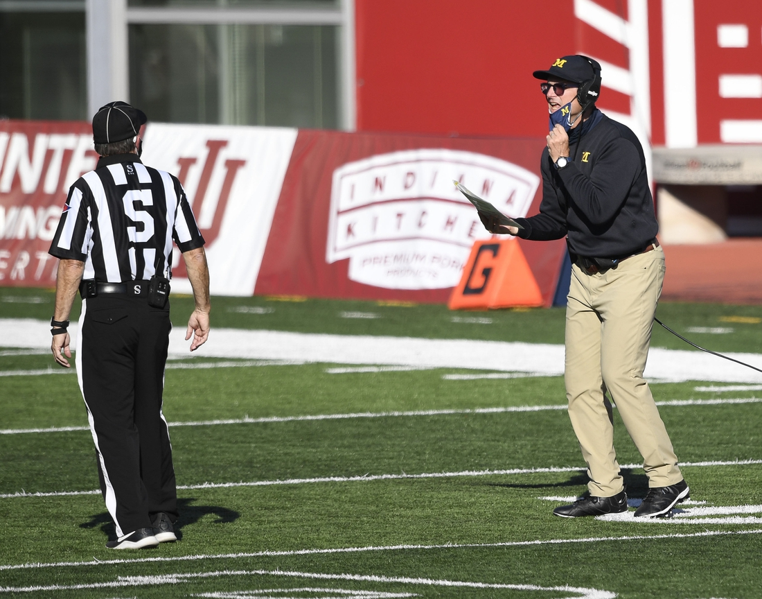 Nov 7, 2020; Bloomington, Indiana, USA; Michigan Wolverines head coach Jim Harbaugh talks to a referee during the second half of the game at Memorial Stadium. The Indiana Hoosiers defeated the Michigan Wolverines 38 to 21. Mandatory Credit: Marc Lebryk-USA TODAY Sports