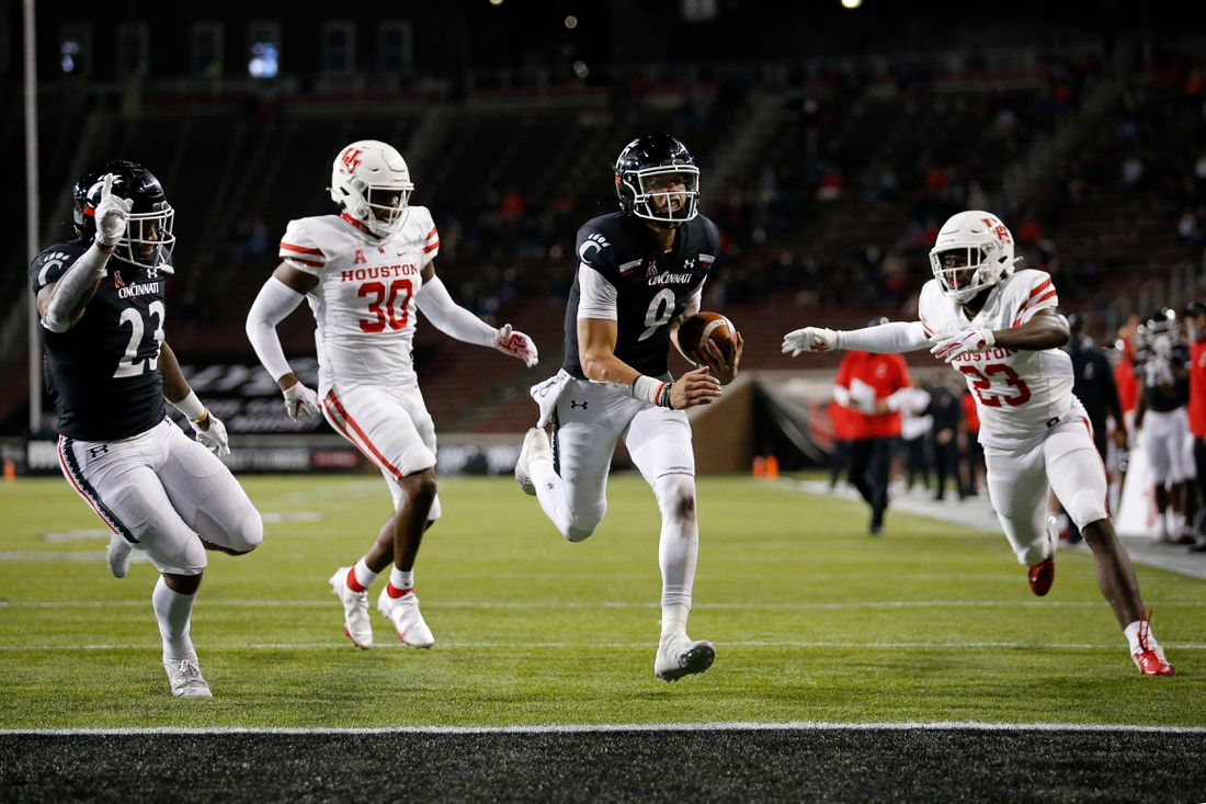 Nov 7, 2020; Cincinnati, Ohio, USA;   Cincinnati Bearcats quarterback Desmond Ridder (9) runs in his third touchdown of the night in the fourth quarter of the American Athletic Conference football game between the University of Houston Cougars and the University of Cincinnati Bearcats at Nippert Stadium in Cincinnati on Saturday, Nov. 7, 2020. The Bearcats continued their undefeated campaign with a 38-10 win over Houston. Mandatory Credit: Sam Greene-USA TODAY NETWORK