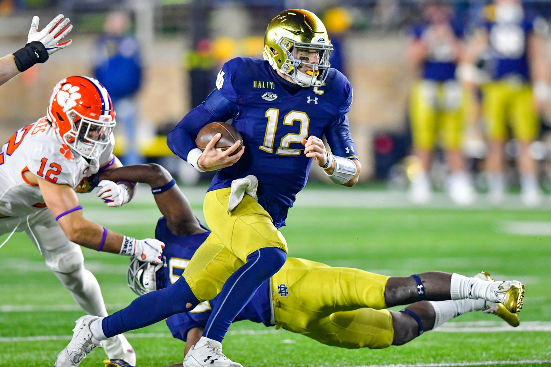 Nov 7, 2020; South Bend, Indiana, USA; Notre Dame Fighting Irish quarterback Ian Book (12) runs the ball in the second overtime period as Clemson Tigers safety Tyler Venables (12) pursues at Notre Dame Stadium. Notre Dame defeated Clemson 47-40 in two overtimes. Mandatory Credit: Matt Cashore-USA TODAY Sports