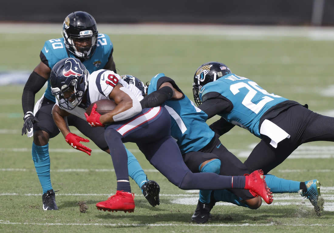 Nov 8, 2020; Jacksonville, Florida, USA;  Houston Texans wide receiver Randall Cobb (18) is tackled by Jacksonville Jaguars cornerback Chris Claybrooks (27) as safety Daniel Thomas (20) and free safety Jarrod Wilson (26) assist during the first quarter at TIAA Bank Field. Mandatory Credit: Reinhold Matay-USA TODAY Sports