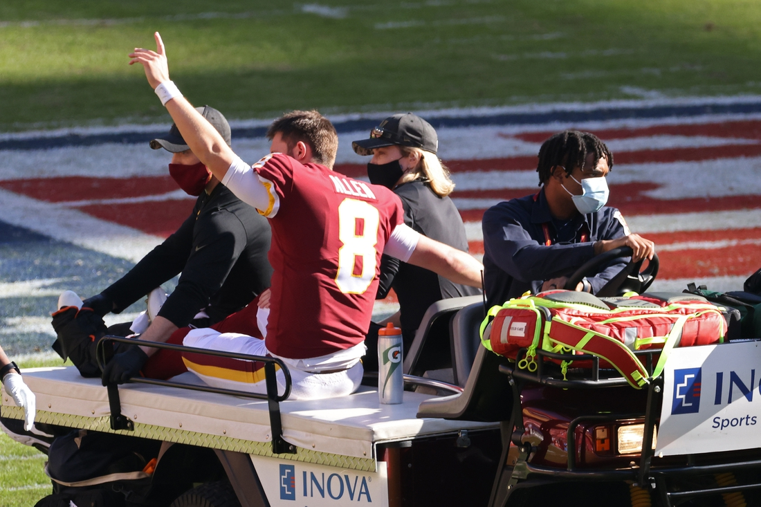 Nov 8, 2020; Landover, Maryland, USA; Washington Football Team quarterback Kyle Allen (8) waves to the crowd from a cart after being injured by being tripped by New York Giants strong safety Jabrill Peppers (not pictured) while scrambling in the first quarter at FedExField. Allen was injured on the play. Mandatory Credit: Geoff Burke-USA TODAY Sports
