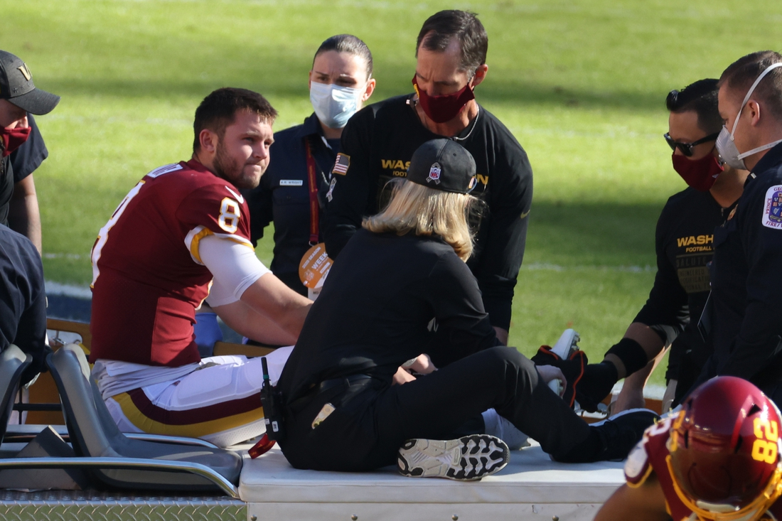 Nov 8, 2020; Landover, Maryland, USA; Washington Football Team quarterback Kyle Allen (8) sits on a cart after being injured by being tripped by New York Giants strong safety Jabrill Peppers (not pictured) while scrambling in the first quarter at FedExField. Allen was injured on the play. Mandatory Credit: Geoff Burke-USA TODAY Sports