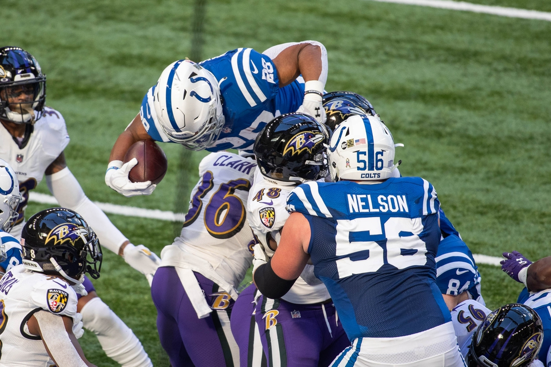 Nov 8, 2020; Indianapolis, Indiana, USA; Indianapolis Colts running back Jonathan Taylor (28) jumps over the Baltimore Ravens defensive line for a touchdown in the first half at Lucas Oil Stadium. Mandatory Credit: Trevor Ruszkowski-USA TODAY Sports