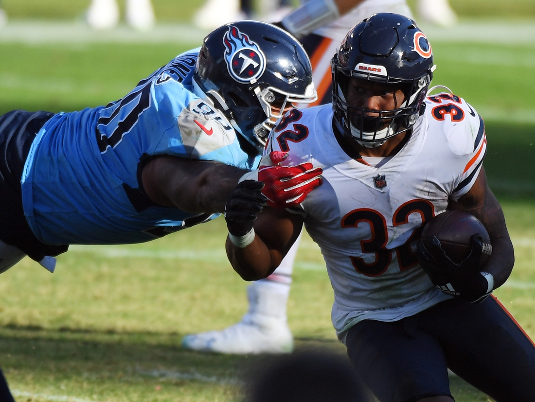 Nov 8, 2020; Nashville, Tennessee, USA; Chicago Bears running back David Montgomery (32) gets away from a tackle attempt from Tennessee Titans defensive tackle DaQuan Jones (90) during the second half at Nissan Stadium. Mandatory Credit: Christopher Hanewinckel-USA TODAY Sports