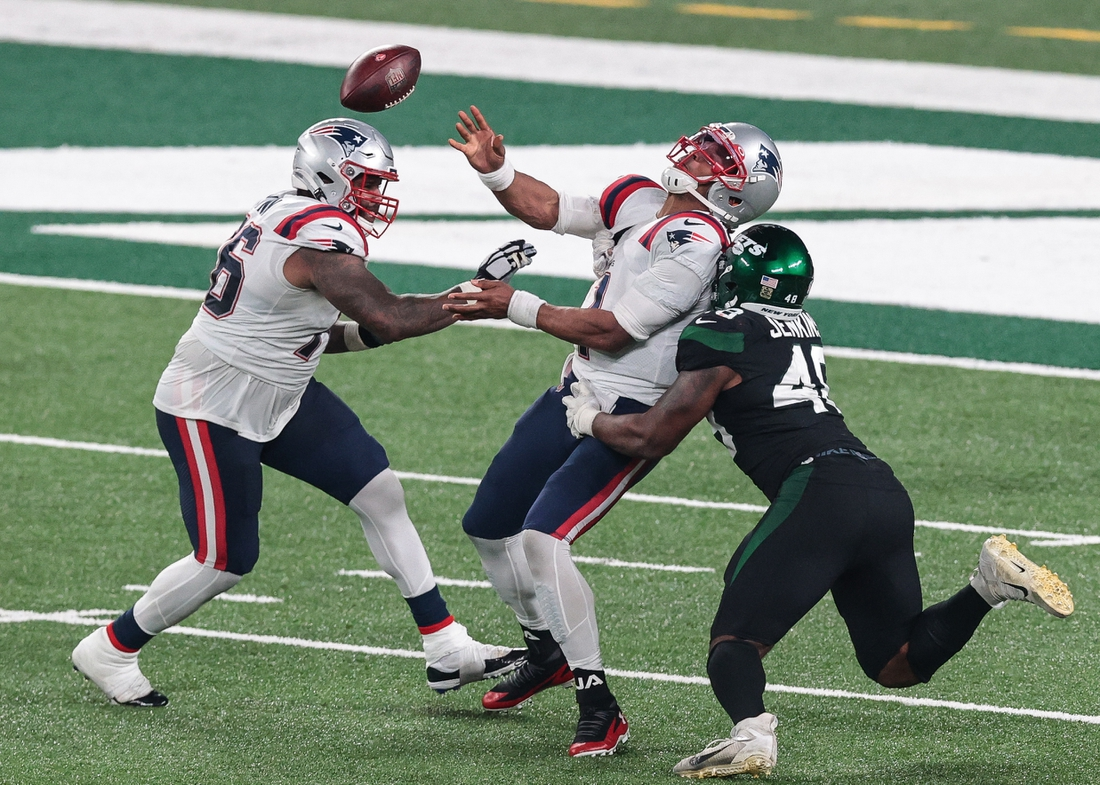 Nov 9, 2020; East Rutherford, New Jersey, USA; New England Patriots quarterback Cam Newton (1) is hit while throwing the ball by New York Jets outside linebacker Jordan Jenkins (48) as offensive tackle Isaiah Wynn (76) blocks during the second half at MetLife Stadium. Mandatory Credit: Vincent Carchietta-USA TODAY Sports