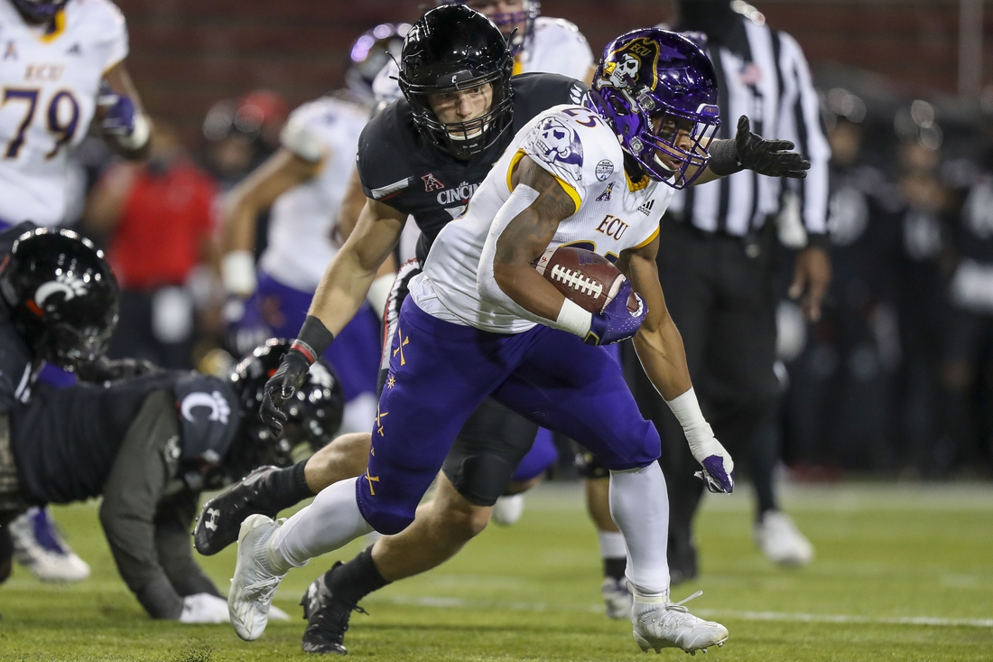 Nov 13, 2020; Cincinnati, Ohio, USA; East Carolina Pirates running back Keaton Mitchell (25) runs with the ball against  Cincinnati Bearcats linebacker Brody Ingle (10) in the first half at Nippert Stadium. Mandatory Credit: Katie Stratman-USA TODAY Sports