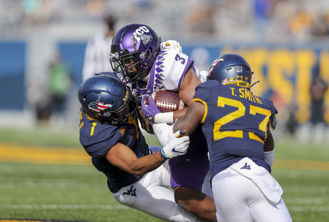 Nov 14, 2020; Morgantown, West Virginia, USA; TCU Horned Frogs running back Emari Demercado (3) is tackled by West Virginia Mountaineers linebacker Tony Fields II (1) and safety Tykee Smith (23) during the second quarter at Mountaineer Field at Milan Puskar Stadium. Mandatory Credit: Ben Queen-USA TODAY Sports