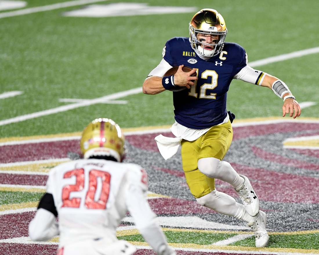 Nov 14, 2020; Chestnut Hill, Massachusetts, USA; Notre Dame Fighting Irish quarterback Ian Book (12) runs with the ball against Boston College Eagles defensive back Elijah Jones (20) during the first half at Alumni Stadium. Mandatory Credit: Brian Fluharty-USA TODAY Sports