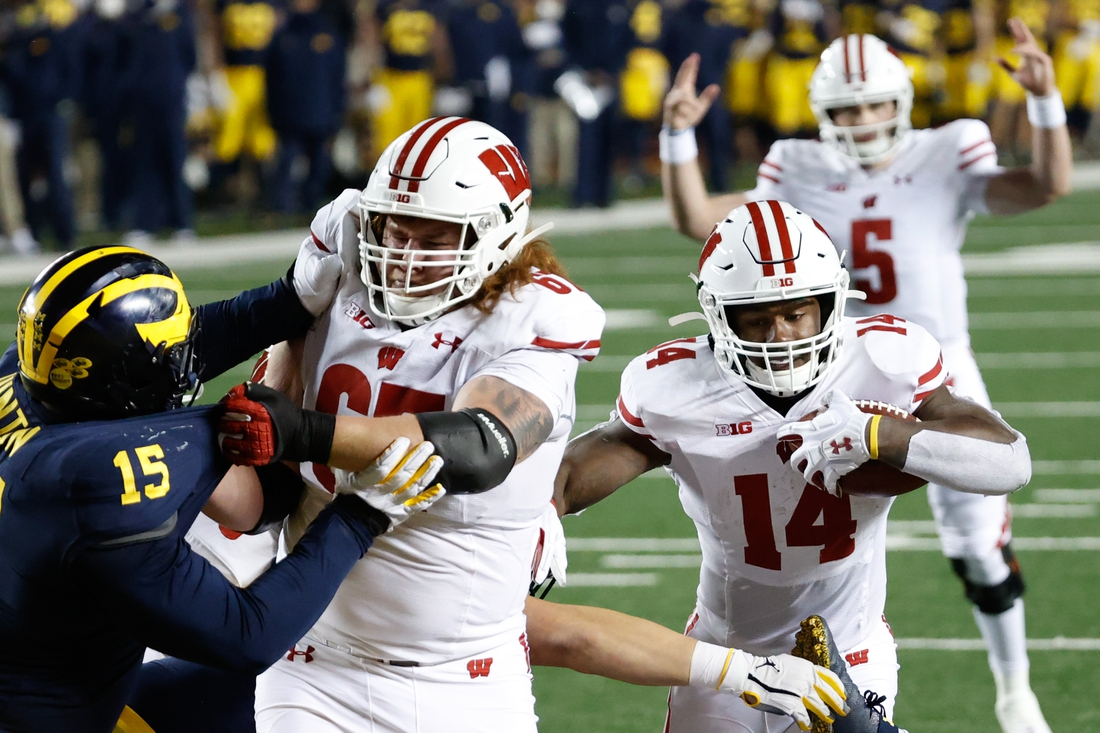 Nov 14, 2020; Ann Arbor, Michigan, USA;  Wisconsin Badgers running back Nakia Watson (14) rushes for a touchdown in the first half against the Michigan Wolverines at Michigan Stadium. Mandatory Credit: Rick Osentoski-USA TODAY Sports