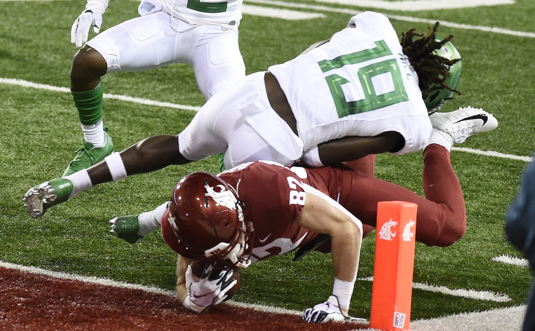 Nov 14, 2020; Pullman, Washington, USA; Washington State Cougars wide receiver Lucas Bacon (82) dives for the goalie for a score against Oregon Ducks safety Jamal Hill (19) in the first half at Martin Stadium. Mandatory Credit: James Snook-USA TODAY Sports
