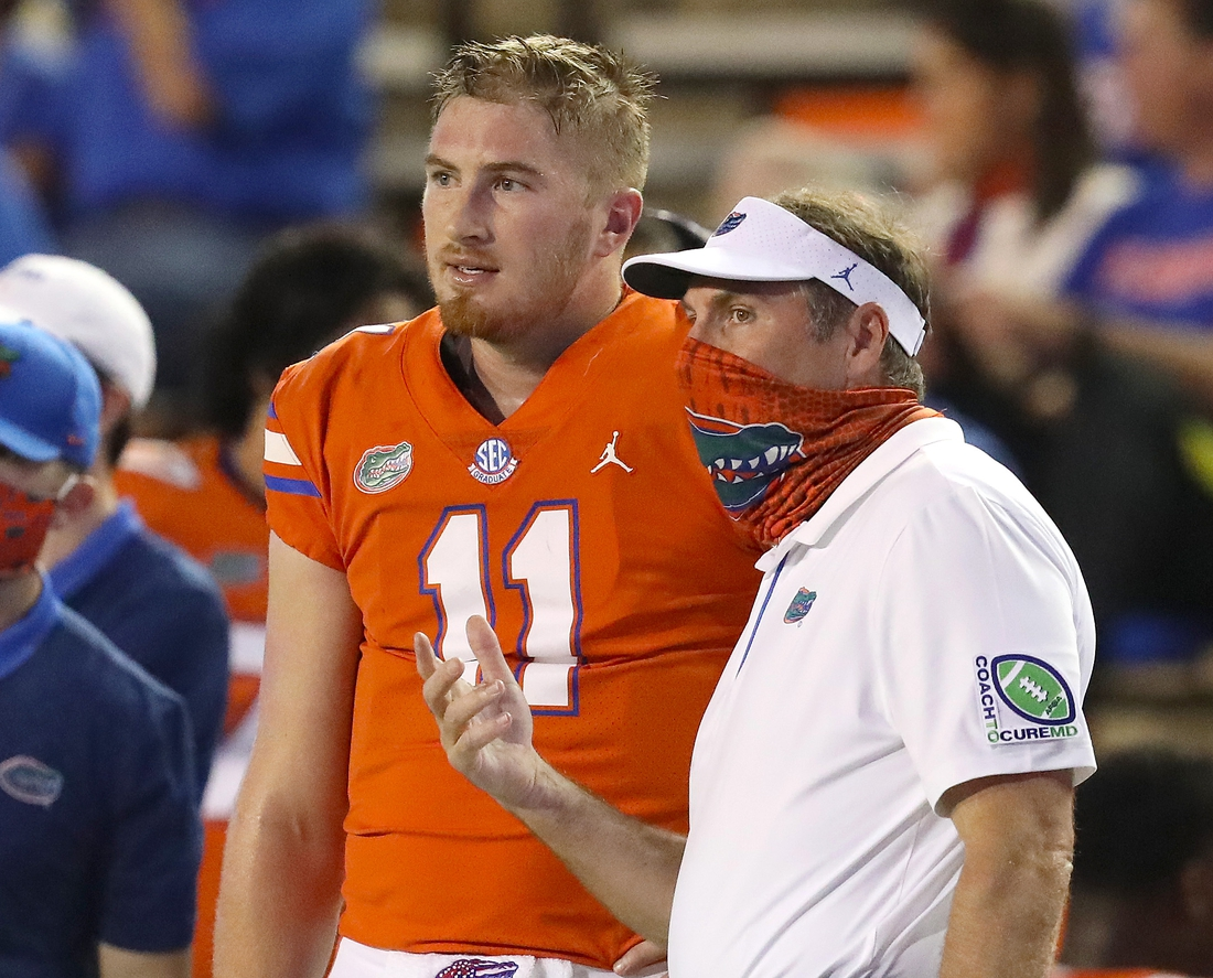 Nov 14, 2020; Gainesville, FL, USA; Florida Gators head coach Dan Mullen talks with quarterback Kyle Trask (11) on the sideline during a football game against Arkansas at Ben Hill Griffin Stadium.  Mandatory Credit: Brad McClenny-USA TODAY NETWORK