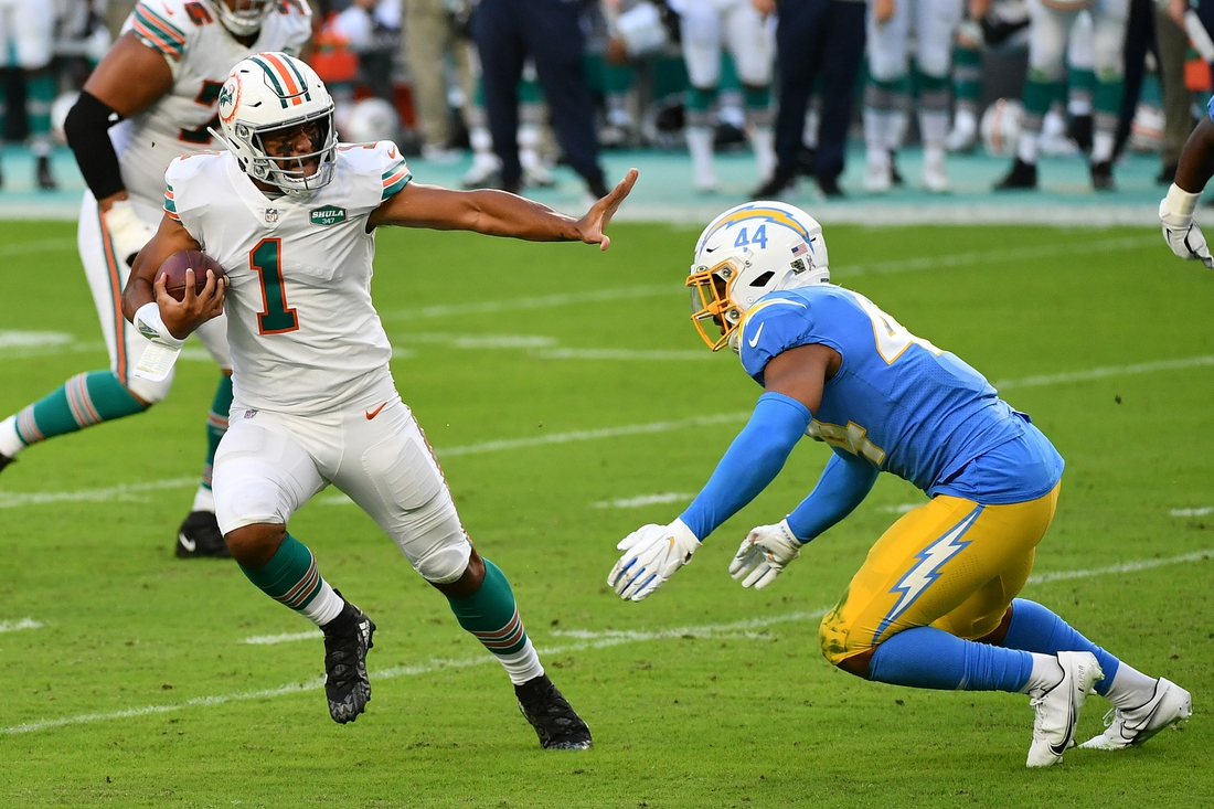 Nov 15, 2020; Miami Gardens, Florida, USA; Miami Dolphins quarterback Tua Tagovailoa (1) scrambles with the ball around Los Angeles Chargers outside linebacker Kyzir White (44) during the first half at Hard Rock Stadium. Mandatory Credit: Jasen Vinlove-USA TODAY Sports