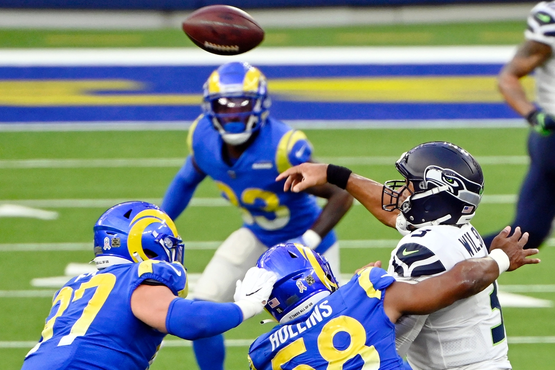Nov 15, 2020; Inglewood, California, USA; Seattle Seahawks quarterback Russell Wilson (3) throws the ball while under pressure by Los Angeles Rams linebacker Justin Hollins (58) during the first half at SoFi Stadium. Mandatory Credit: Robert Hanashiro-USA TODAY Sports