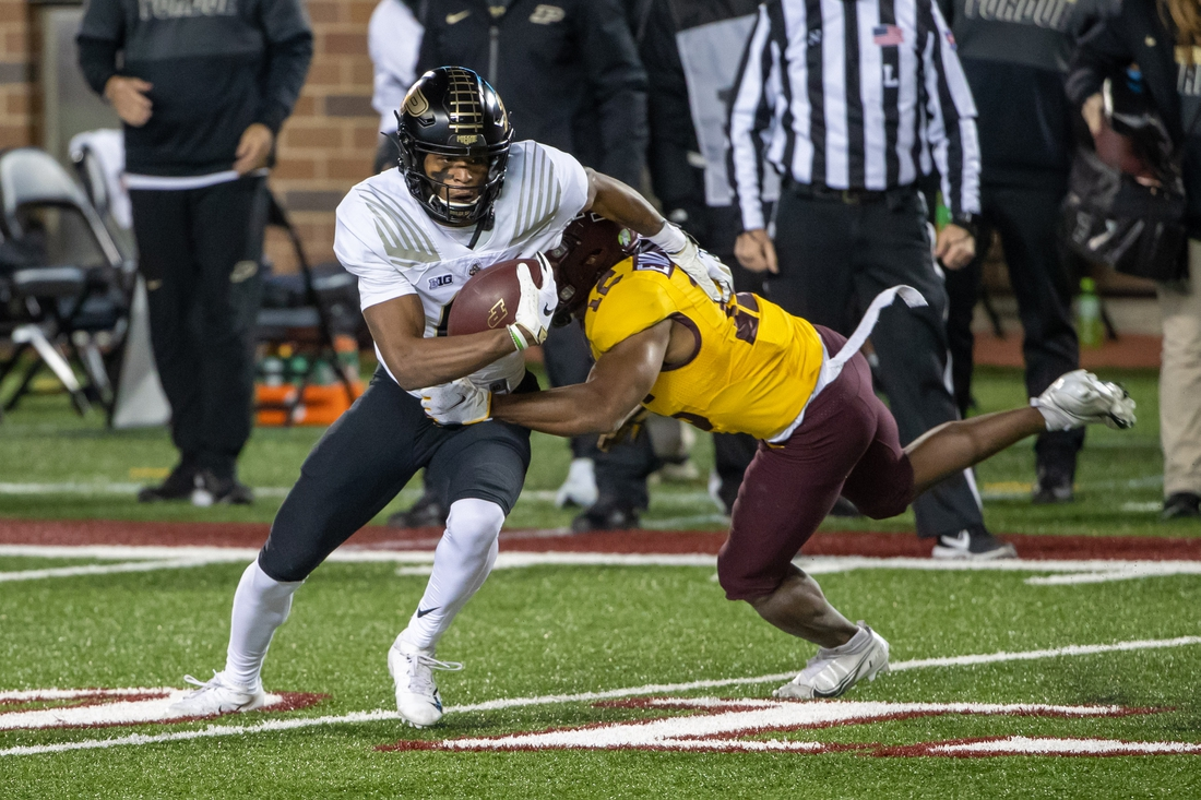 Nov 20, 2020; Minneapolis, Minnesota, USA; Purdue Boilermakers wide receiver Milton Wright (0) catches a pass and gets tackled from Minnesota Golden Gophers defensive back Jalen Glaze (12) in the first quarter at TCF Bank Stadium. Mandatory Credit: Jesse Johnson-USA TODAY Sports