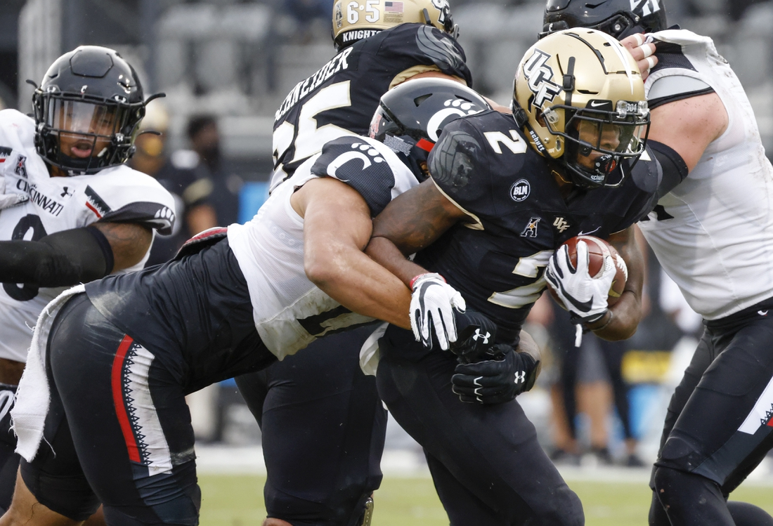 Nov 21, 2020; Orlando, Florida, USA; Cincinnati Bearcats linebacker Darrian Beavers (27) tackles UCF Knights running back Otis Anderson (2) during the first quarter at the Bounce House. Mandatory Credit: Reinhold Matay-USA TODAY Sports