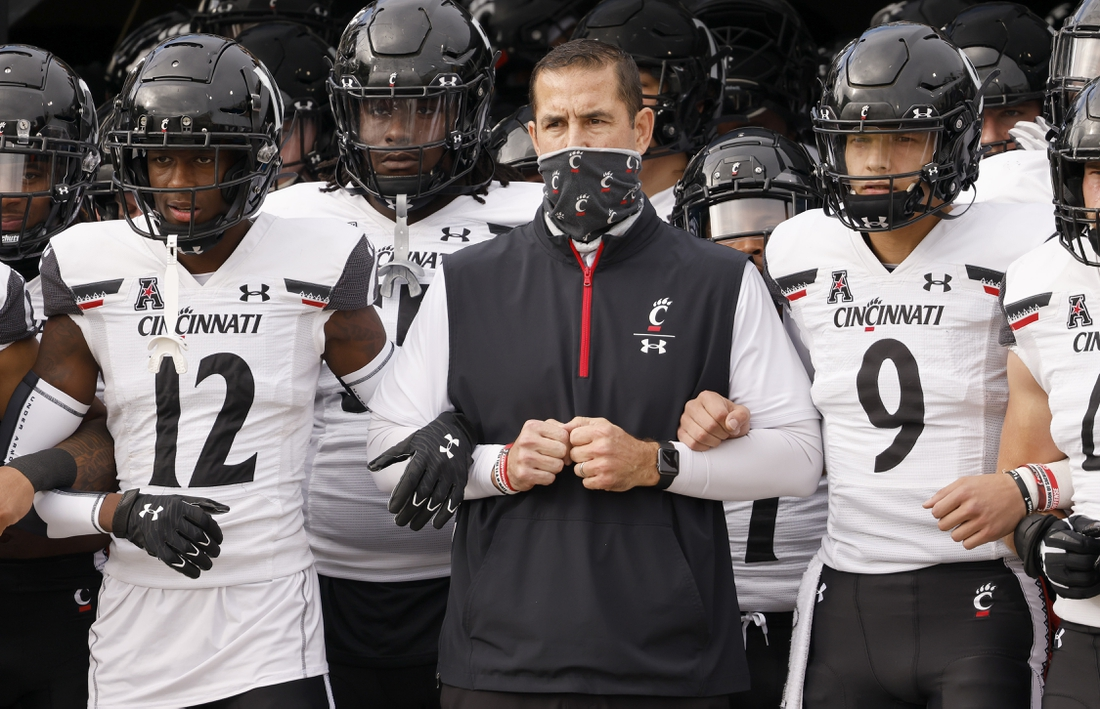 Nov 21, 2020; Orlando, Florida, USA; Cincinnati Bearcats head coach Luke Fickell (middle) and quarterback Desmond Ridder (9) and cornerback Ahmad Gardner (12) lead the team onto the field before the game against the UCF Knights at the Bounce House. Mandatory Credit: Reinhold Matay-USA TODAY Sports