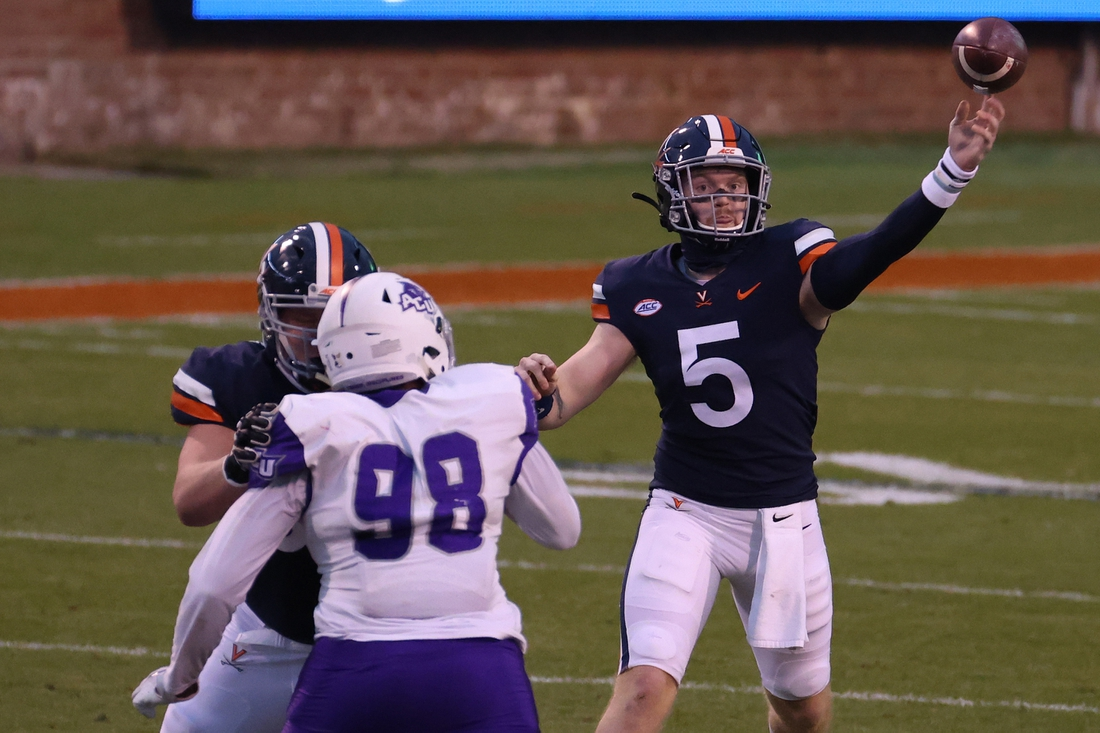 Nov 21, 2020; Charlottesville, Virginia, USA; Virginia Cavaliers quarterback Brennan Armstrong (5) passes the bad as Abilene Christian Wildcats defensive tackle Dre Jones (98) defends in the first quarter at Scott Stadium. Mandatory Credit: Geoff Burke-USA TODAY Sports