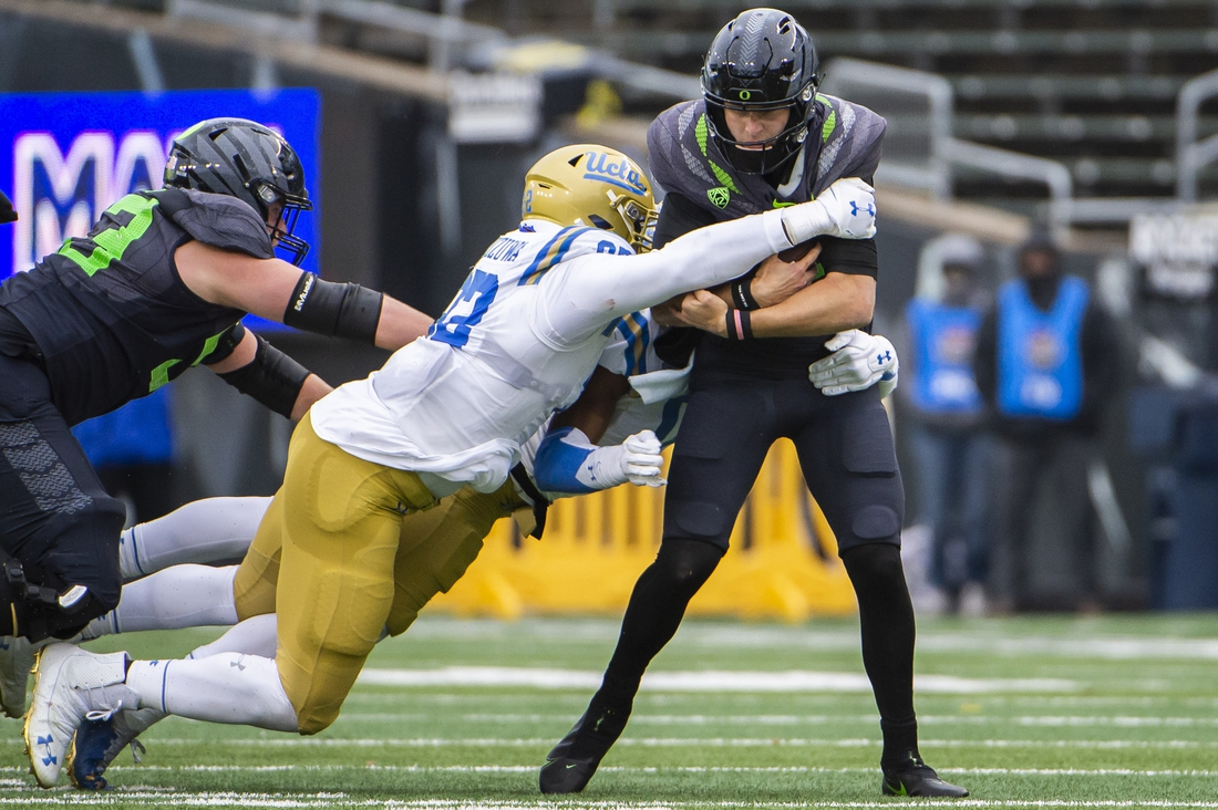 Nov 21, 2020; Eugene, Oregon, USA; UCLA Bruins defensive lineman Osa Odighizuwa (92) sacks Oregon Ducks quarterback Tyler Shough (12) during the first half at Autzen Stadium. The Ducks won 38-35. Mandatory Credit: Troy Wayrynen-USA TODAY Sports