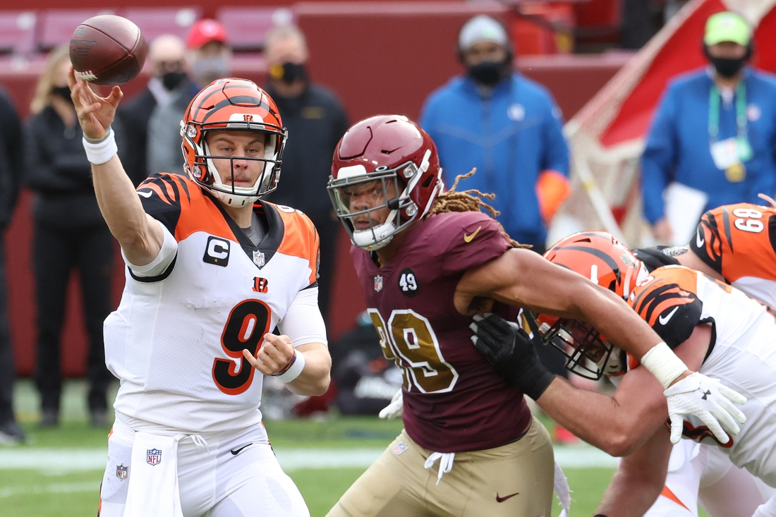Nov 22, 2020; Landover, Maryland, USA; Cincinnati Bengals quarterback Joe Burrow (9) passes the ball under pressure from Washington Football Team defensive end Chase Young (99) in the second quarter at FedExField. Mandatory Credit: Geoff Burke-USA TODAY Sports