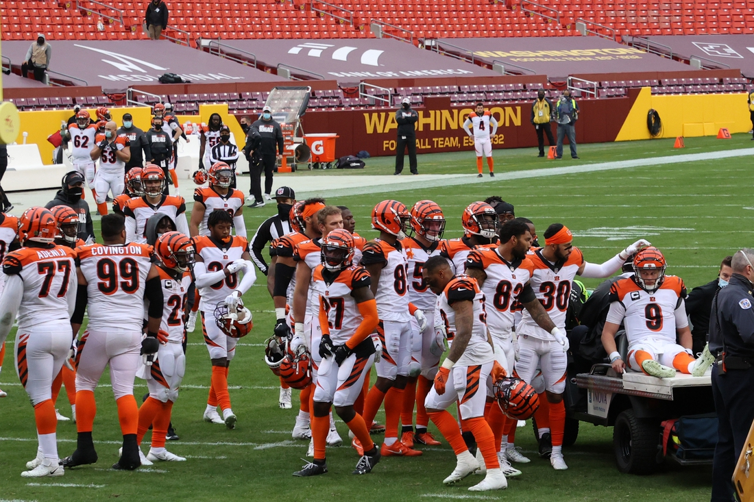 Nov 22, 2020; Landover, Maryland, USA; Cincinnati Bengals quarterback Joe Burrow (9) is consoled by teammates prior to being carted off the field after injuring his left knee against the Washington Football Team in the third quarter at FedExField. Mandatory Credit: Geoff Burke-USA TODAY Sports