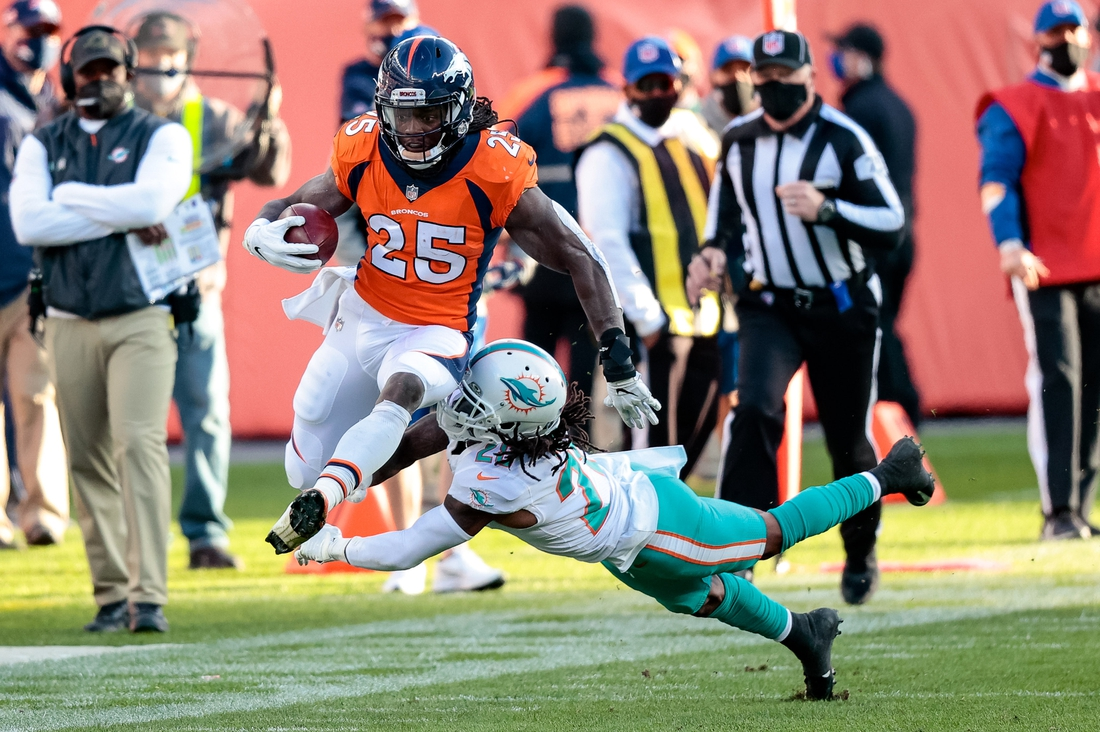 Nov 22, 2020; Denver, Colorado, USA; Denver Broncos running back Melvin Gordon III (25) runs through the tackle of Miami Dolphins safety Bobby McCain (28) in the second quarter at Empower Field at Mile High. Mandatory Credit: Isaiah J. Downing-USA TODAY Sports