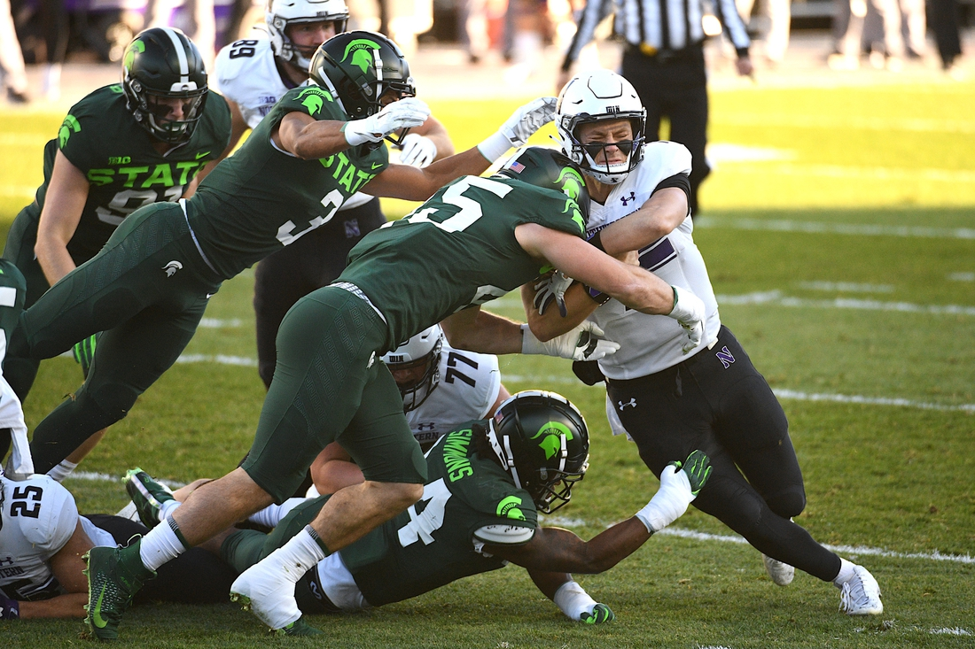 Nov 28, 2020; East Lansing, Michigan, USA; Northwestern Wildcats quarterback Peyton Ramsey (12) runs the ball as he is tackled by Michigan State Spartans linebacker Noah Harvey (45) during the first quarter at Spartan Stadium. Mandatory Credit: Tim Fuller-USA TODAY Sports