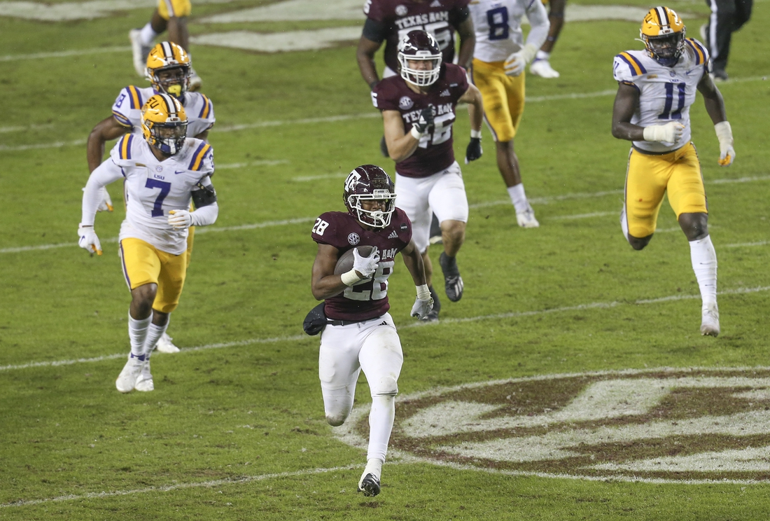 Nov 28, 2020; College Station, Texas, USA; Texas A&M Aggies running back Isaiah Spiller (28) rushes for a touchdown against the LSU Tigers in the first quarter at Kyle Field. Mandatory Credit: Thomas Shea-USA TODAY Sports
