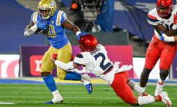 Nov 28, 2020; Pasadena, California, USA; UCLA Bruins running back Demetric Felton (10) stiff arms Arizona Wildcats defensive back Lorenzo Burns (2) during a first quarter running play at Rose Bowl. Mandatory Credit: Robert Hanashiro-USA TODAY Sports
