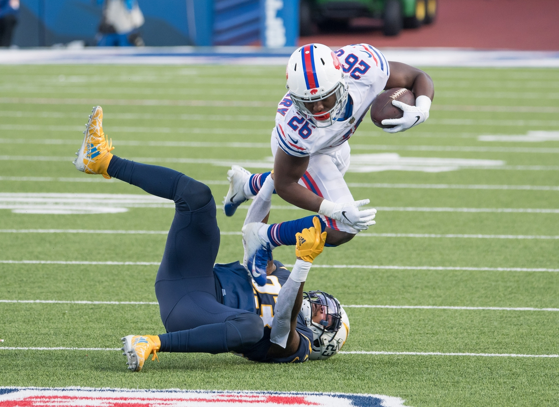 Nov 29, 2020; Orchard Park, New York, USA; Buffalo Bills running back Devin Singletary (26) is tackled by Los Angeles Chargers strong safety Rayshawn Jenkins (23) in the second quarter at Bills Stadium. Mandatory Credit: Mark Konezny-USA TODAY Sports