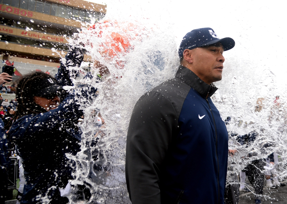 Dec 15, 2018; Albuquerque, NM, USA; Utah State Aggies interim coach Frank Maile is doused with water after the game against the North Texas Mean Green of the New Mexico Bowl at Dreamstyle Stadium. Mandatory Credit: Joe Camporeale-USA TODAY Sports