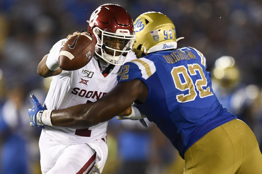 Sep 14, 2019; Pasadena, CA, USA; Oklahoma Sooners quarterback Jalen Hurts (1) moves the ball while UCLA Bruins defensive lineman Osa Odighizuwa (92) defends during the second half at Rose Bowl. Mandatory Credit: Kelvin Kuo-USA TODAY Sports