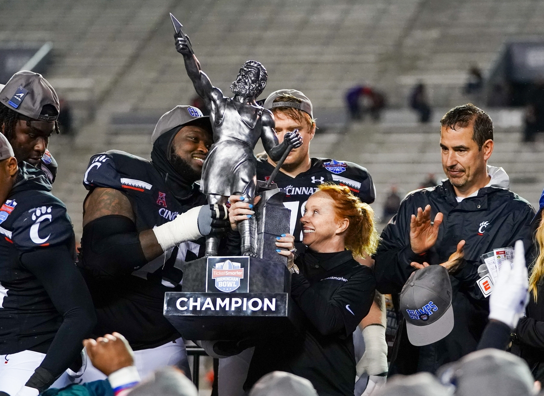 Jan 2, 2020; Birmingham, Alabama, USA; Cincinnati Bearcats offensive lineman Chris Ferguson (75) accepts the trophy from Ticketsmarter.com president Heather Goodman (right) after defeating the Boston College Eagles at Legion Field. Mandatory Credit: Marvin Gentry-USA TODAY Sports