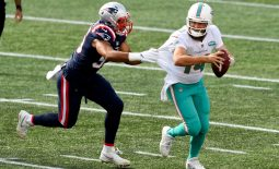 Sep 13, 2020; Foxborough, Massachusetts, USA; Miami Dolphins quarterback Ryan Fitzpatrick (14) runs under pressure from New England Patriots defensive end Derek Rivers (95) during the second half at Gillette Stadium. Mandatory Credit: Brian Fluharty-USA TODAY Sports
