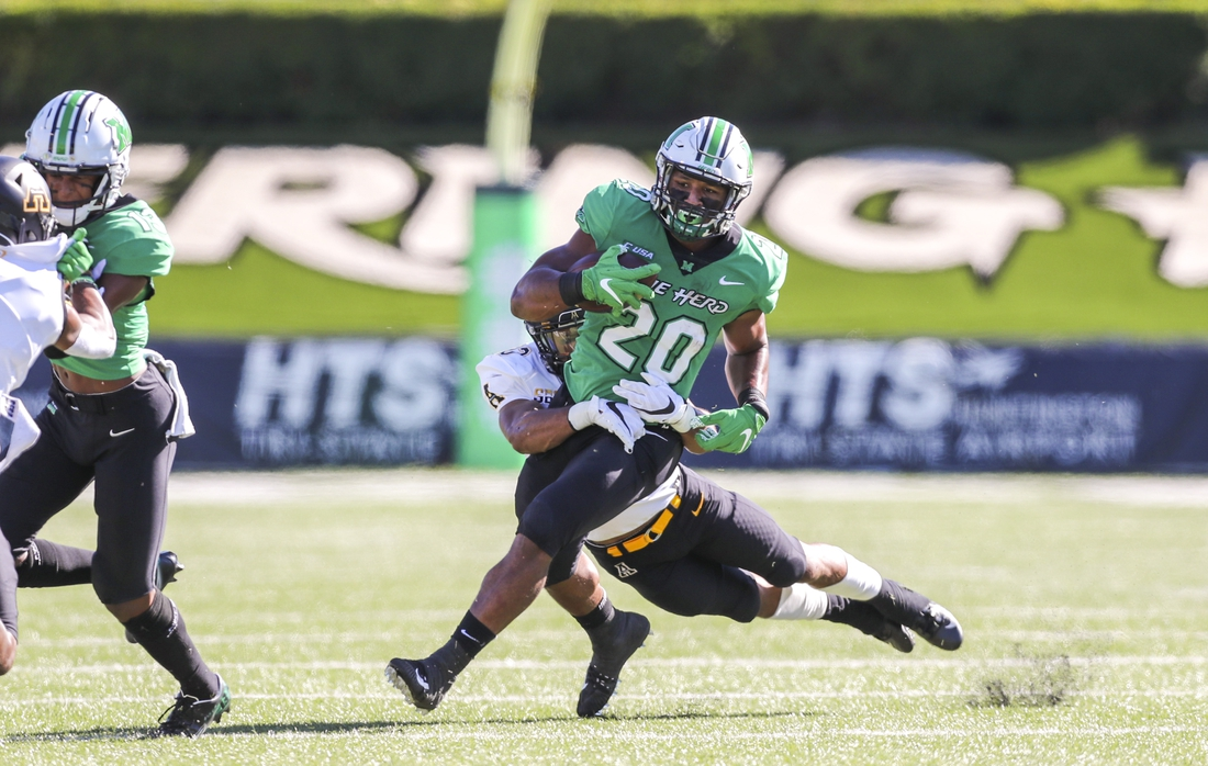 Sep 19, 2020; Huntington, West Virginia, USA; Marshall Thundering Herd running back Brenden Knox (20) runs the ball and is tackled by Appalachian State Mountaineers defensive back Kaiden Smith (13) during the first quarter at Joan C. Edwards Stadium. Mandatory Credit: Ben Queen-USA TODAY Sports