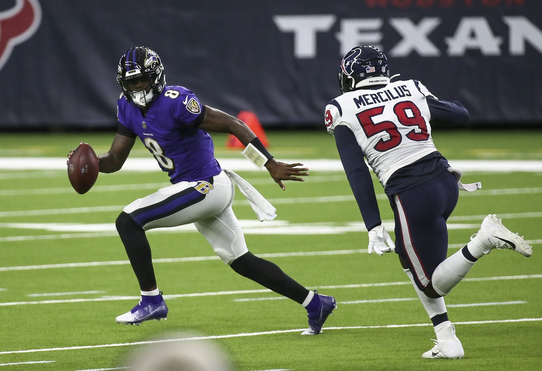 Sep 20, 2020; Houston, Texas, USA; Baltimore Ravens quarterback Lamar Jackson (8) rolls out of the pocket with the ball as Houston Texans outside linebacker Whitney Mercilus (59) applies defensive pressure during the second quarter at NRG Stadium. Mandatory Credit: Troy Taormina-USA TODAY Sports