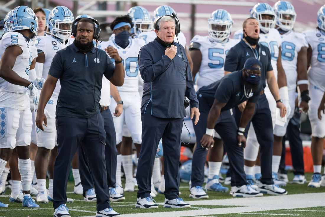Oct 3, 2020; Chestnut Hill, Massachusetts, USA; North Carolina Tar Heels head coach Mack Brown pulls down his face mask while calling out to the field against the Boston College Eagles at Alumni Stadium. Mandatory Credit: Adam Richins-USA TODAY Sports