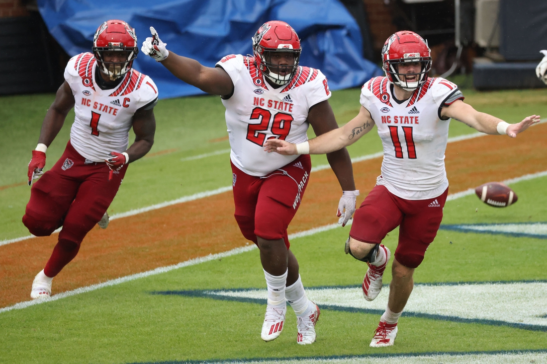 Oct 10, 2020; Charlottesville, Virginia, USA; North Carolina State Wolfpack defensive tackle Alim McNeill (29) celebrates with Wolfpack linebacker Isaiah Moore (1) and Wolfpack linebacker Payton Wilson (11) after returning an interception for a touchdown against the Virginia Cavaliers in the fourth quarter at Scott Stadium. Mandatory Credit: Geoff Burke-USA TODAY Sports