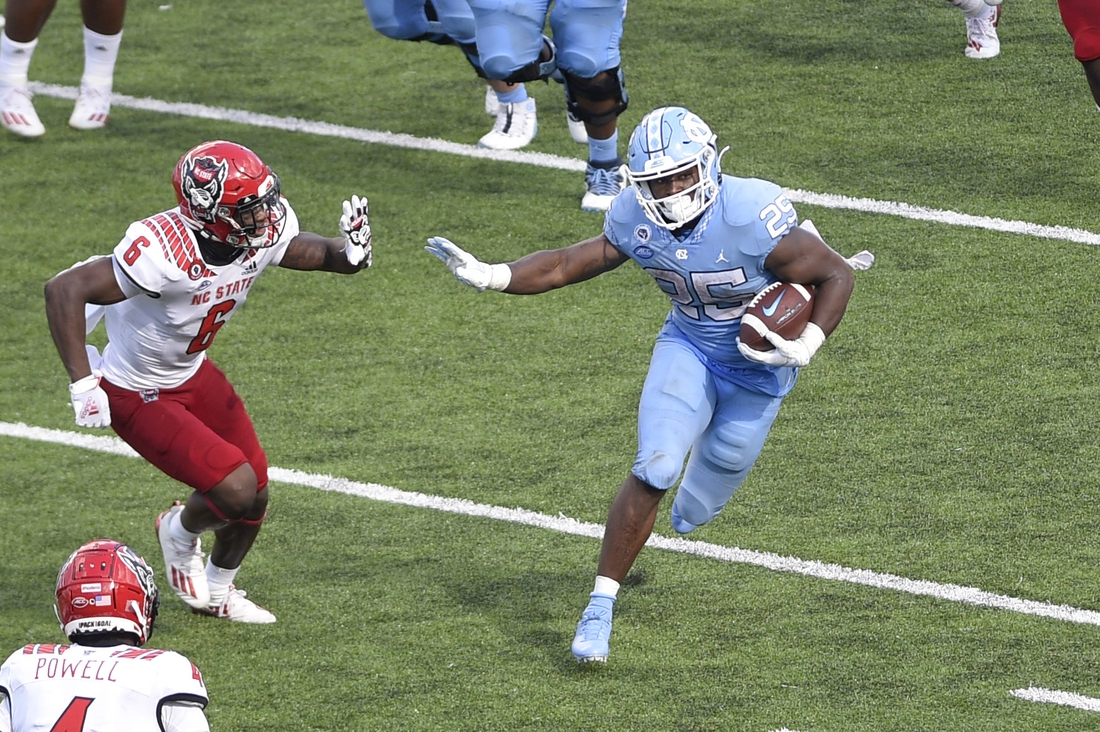 Oct 24, 2020; Chapel Hill, North Carolina, USA; North Carolina Tar Heels running back Javonte Williams (25) runs for a touchdown as North Carolina State Wolfpack safety Jakeen Harris (6) defends in the fourth quarter at Kenan Memorial Stadium. Mandatory Credit: Bob Donnan-USA TODAY Sports