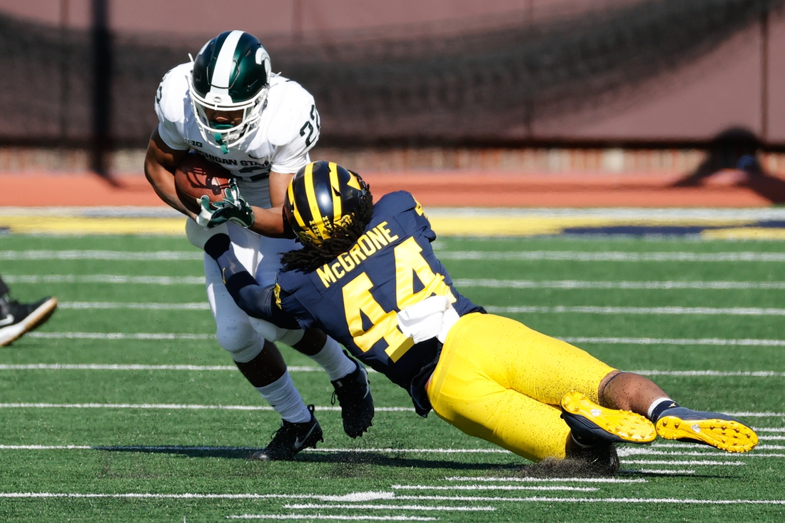 Oct 31, 2020; Ann Arbor, Michigan, USA;  Michigan State Spartans running back Jordon Simmons (22) is tackled by DUPLICATE***Michigan Wolverines defensive back Joshua Luther (44)***Michigan Wolverines linebacker Cameron McGrone (44) in the first half at Michigan Stadium. Mandatory Credit: Rick Osentoski-USA TODAY Sports