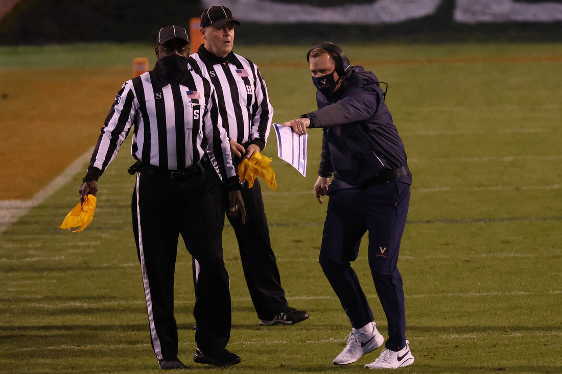 Oct 31, 2020; Charlottesville, Virginia, USA; Virginia Cavaliers coach Bronco Mendenhall (R) argues a call with officials against the North Carolina Tar Heels in the second quarter at Scott Stadium. Mandatory Credit: Geoff Burke-USA TODAY Sports