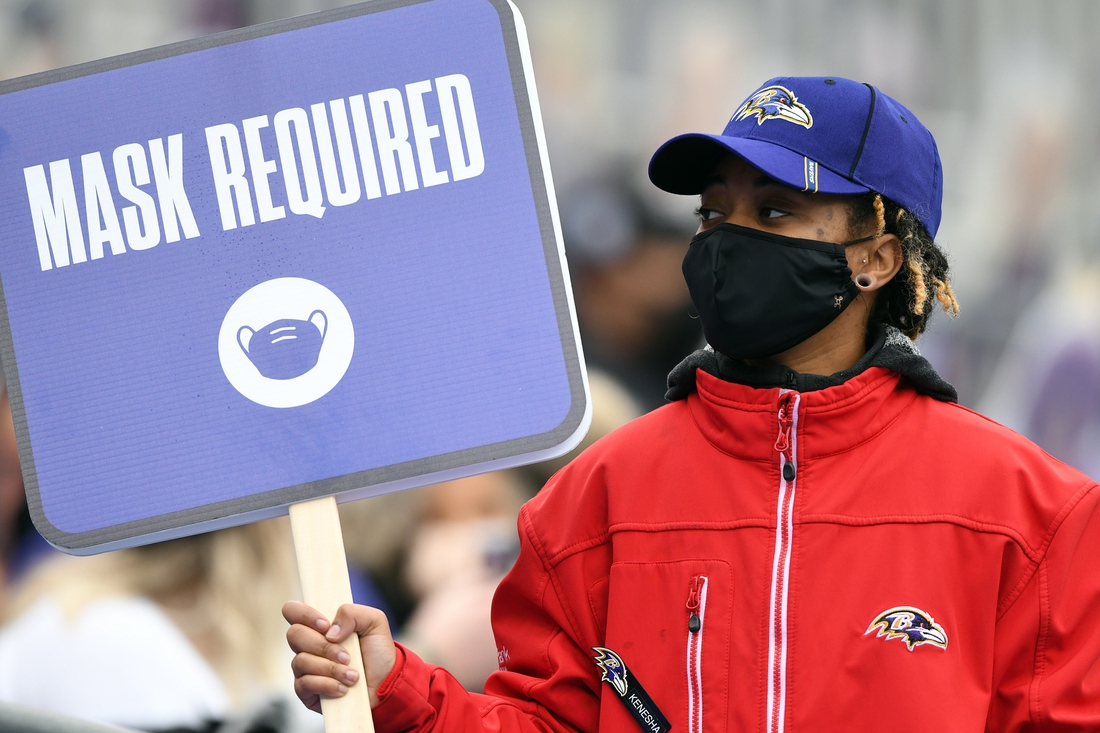 Nov 1, 2020; Baltimore, Maryland, USA;  A member of M&T Bank Stadium security holds up a sign reminding patrons to wear masks during a game between the Pittsburgh Steelers amd Baltimore Ravens. Mandatory Credit: Mitchell Layton-USA TODAY Sports